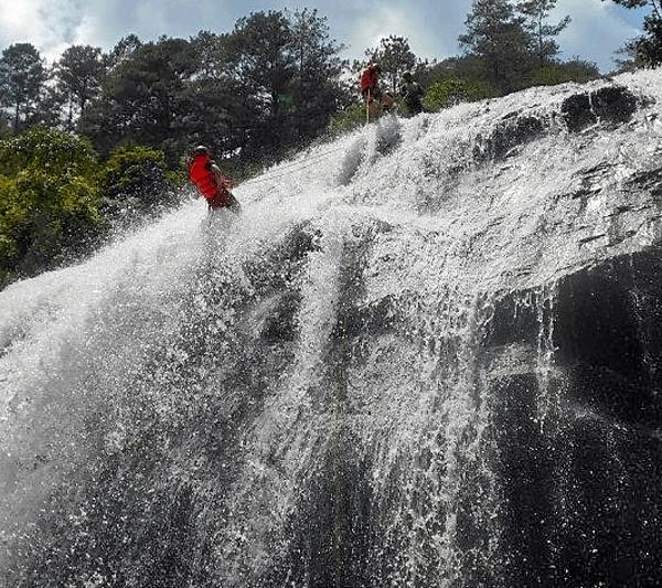 So überwindest du auf Reisen deine eigene Grenzen, z. B. beim Canyoning. - Breiter Wasserfall, den sich zwei Personen hinab abseilen.