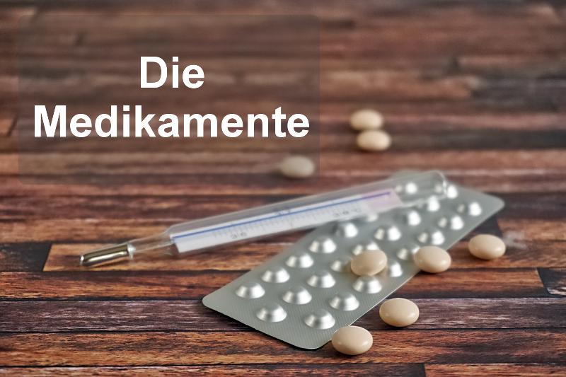Ein paar lose Dragees, ein Blister mit Tabletten und ein Fieberthermometer stehen für die Reiseapotheke, die man auf Reisen dabei haben sollte.