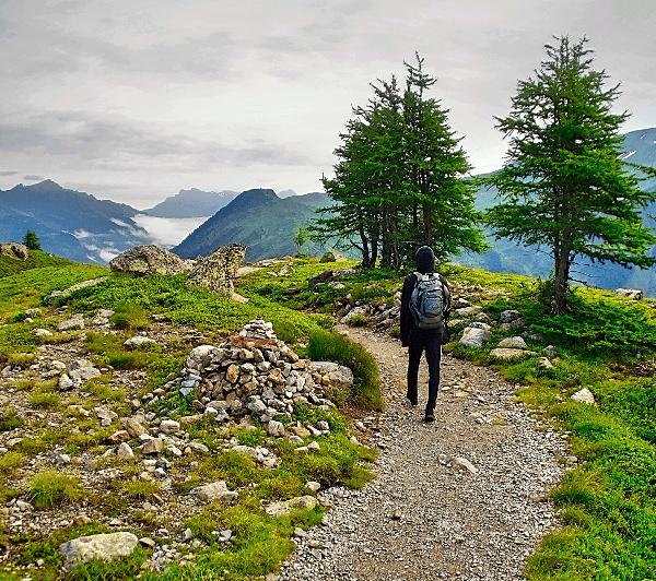 Du musst als Alleinreisende nicht einsam unterwegs sein. Einsame Frau auf einem Wanderweg in den Bergen.