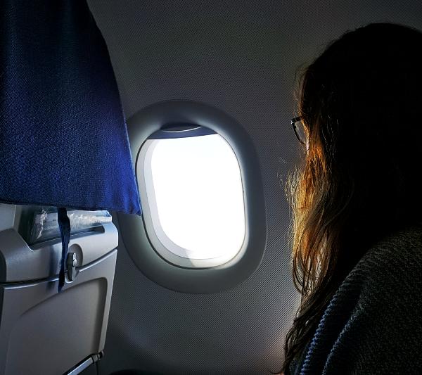 Frau in einem Flugzeug, die auf einem Fensterplatz sitzt und aus dem Fenster schaut.