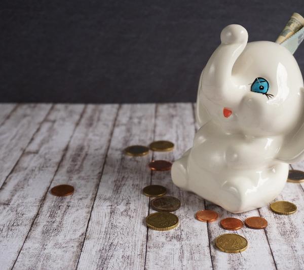 Spardose aus der ein Geldschein herausragt. Auf dem Tisch liegen Münzen. Wer billig seine Flugtickets bucht, hat mehr Geld in der Reisekasse übrig.