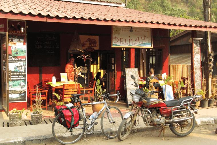 Das Hostel Delilah in Nong Kiao. Vor einem leuchtend rot angestrichenen Haus stehen Tische mit Stühlen, auf denen Leute sitzen. Auf der Straße davor stehen ein Fahrrad und ein Motorrad.