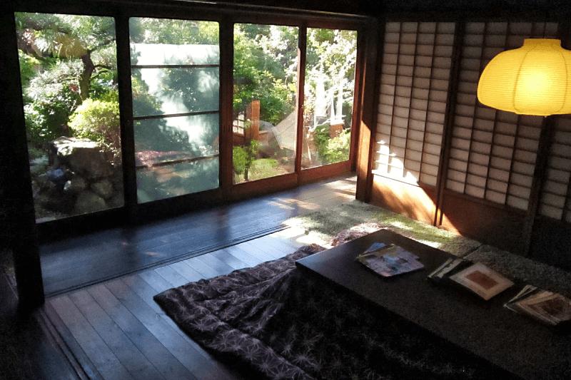 Der Aufenthaltsraum in einem traditionellen japanischen Holzhaus, mit Blick auf den japanischen Garten.