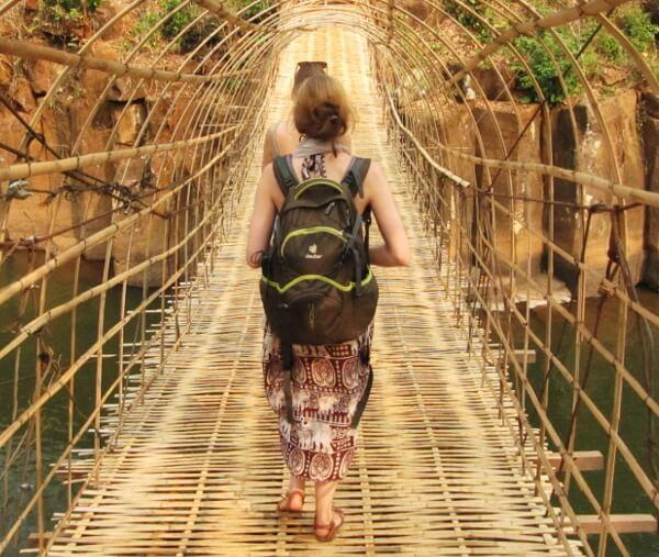 6 Tipps, die dir das Reisen mit dem Rucksack erleichtern - zwei Frauen mit Rucksack überqueren eine wackelige Bambusbrücke