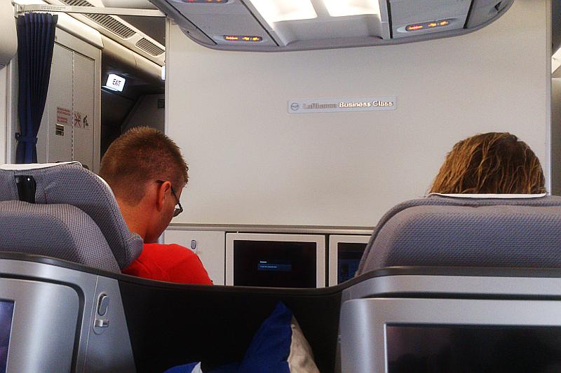 Rückansicht zweier Personen im Flugzeug. An der vorderen Wand steht Lufthansa Business Class.
