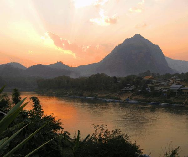 Der Ort Nong Kiao vor einem Karstberg. Im Hintergrund gehst die Sonne unter und im Vordergrund glänzt der Fluss in der Abendsonne.