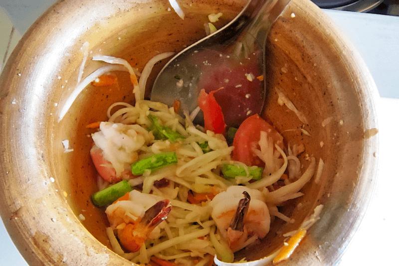 Der scharfe Papayasalat ist eines der bekanntesten Street Foods Thailands. Papayasalat im Mörser.