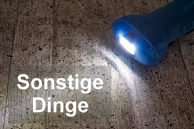 Eine Taschenlampe leuchtet einen Betonboden an und steht stellvertretend für die Dinge, die ein Reisender sonst noch braucht.