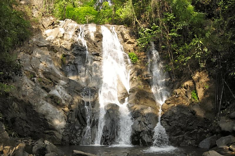Ein Felsen im Dschungel über den ein Wasserfall in ein Wasserbecken fällt.